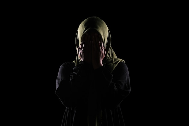 Mulher muçulmana asiática cobrir o rosto com a mão, conceito de parar a violência contra as mulheres.