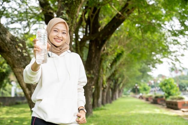Mulher muçulmana asiática com lenço na cabeça bebendo uma garrafa de água durante exercícios ao ar livre