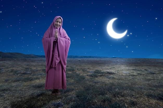 Mulher muçulmana asiática com véu e gesto de saudação com a cena noturna de fundo