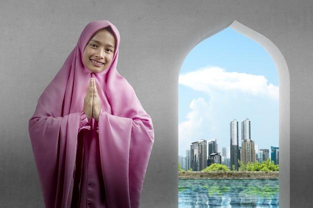 Mulher muçulmana asiática com véu e gesto de saudação na mesquita