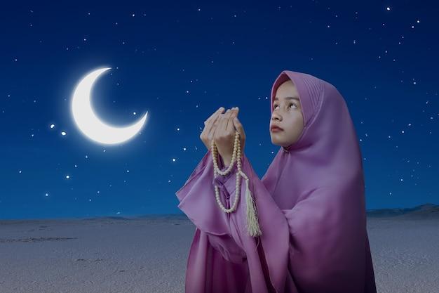 Mulher muçulmana asiática com véu orando com contas de oração nas mãos e a cena noturna de fundo
