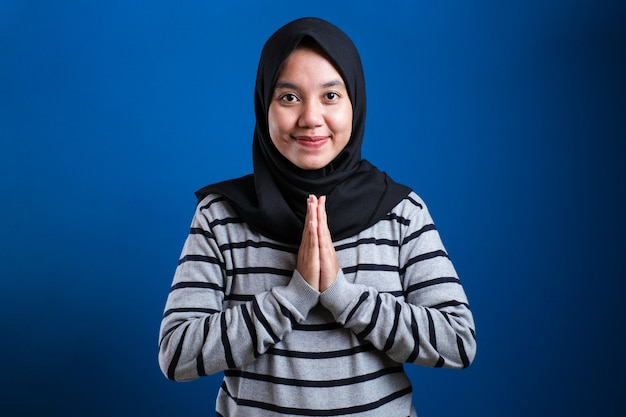 Mulher muçulmana asiática dando as boas-vindas aos convidados gesto sobre fundo azul
