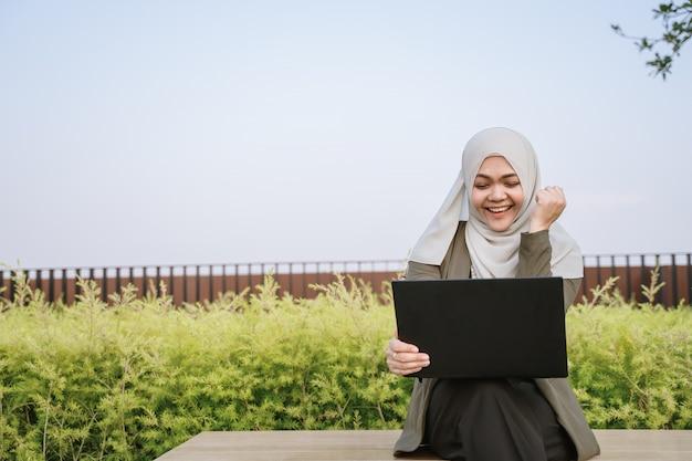 Mulher muçulmana asiática do vencedor eufórico no terno verde e trabalho em um computador no parque.