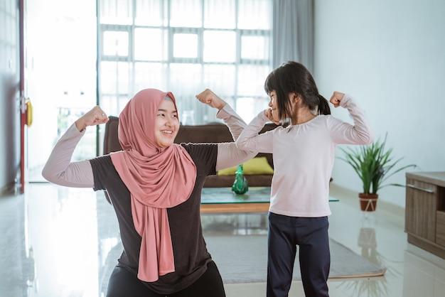Mulher muçulmana asiática e filha fazendo exercícios e esportes em casa durante o isolamento