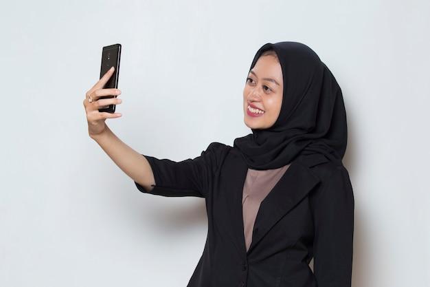 Mulher muçulmana asiática em hijab com telefone celular fazendo selfie
