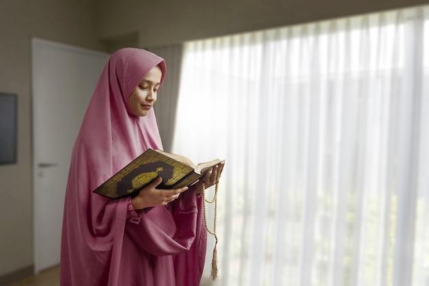 Mulher muçulmana asiática em um véu segurando contas de oração e lendo o alcorão
