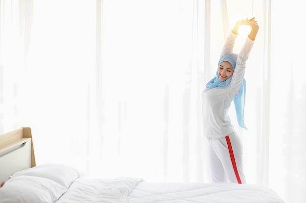 Mulher muçulmana asiática esticando os braços ao nascer do sol.