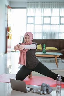 Mulher muçulmana asiática fazendo exercícios e esportes em casa
