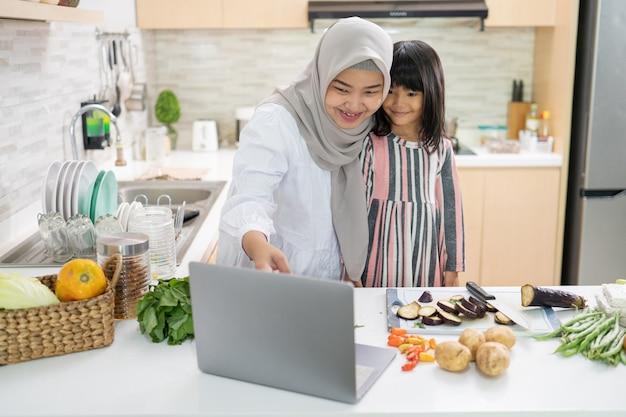 Mulher muçulmana asiática feliz com sua filha cozinhando juntas na cozinha