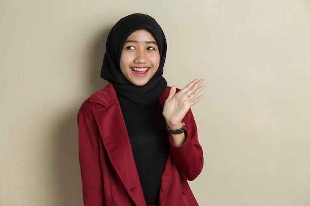 Mulher muçulmana asiática feliz dizendo olá no fundo cinza