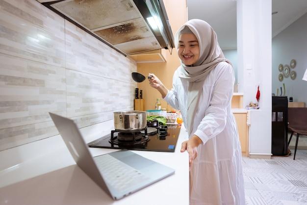 Mulher muçulmana asiática feliz olhando para seu laptop aprendendo a cozinhar um prato em casa