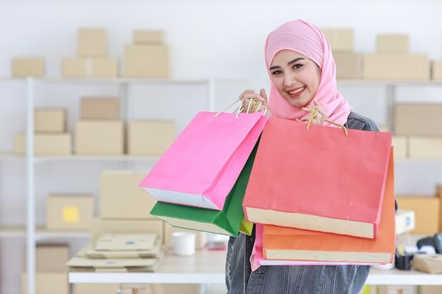 Mulher muçulmana asiática grávida ativa em um vestido casual em pé e segurando sacolas de compras com entrega de caixa de pacote online