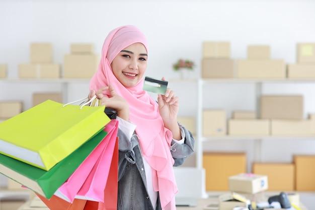 Mulher muçulmana asiática inteligente ativa no casaco de brim em pé e segurando sacolas de compras enquanto mostra o cartão de crédito com fundo de entrega de caixa de pacote on-line. menina bonita olhando cemera e sorriso.