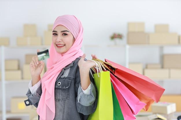 Mulher muçulmana asiática inteligente ativa no casaco de brim em pé e segurando sacolas de compras enquanto mostra o cartão de crédito