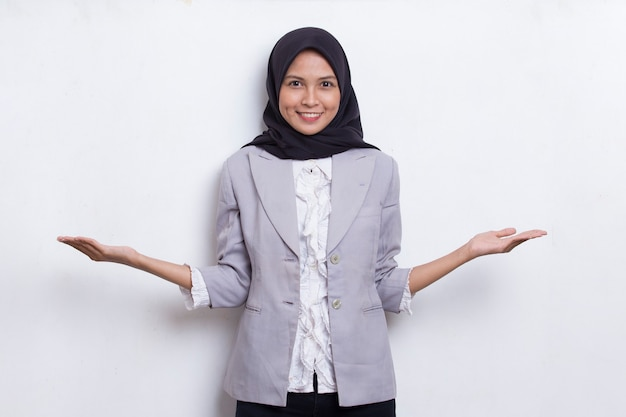 Mulher muçulmana asiática jovem feliz apontando com os dedos para diferentes direções, isoladas no branco