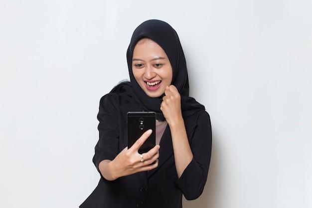 Mulher muçulmana asiática jovem feliz usando telefone celular