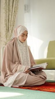 Mulher muçulmana asiática lendo alcorão sério