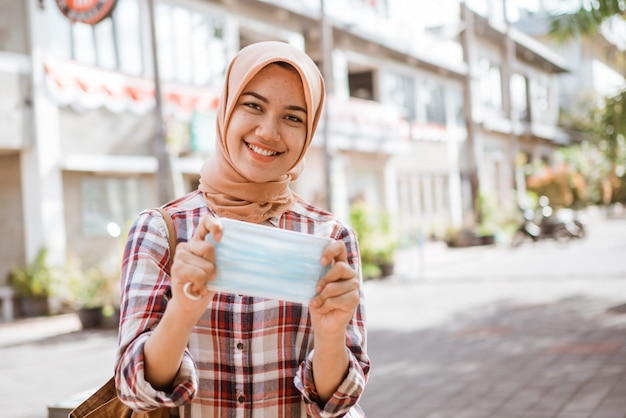 Mulher muçulmana asiática mostrando máscara ao ar livre