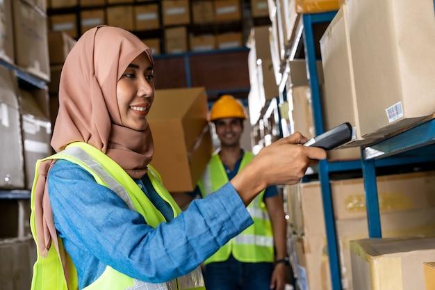 Mulher muçulmana asiática no depósito faz inventário com leitor de código de barras