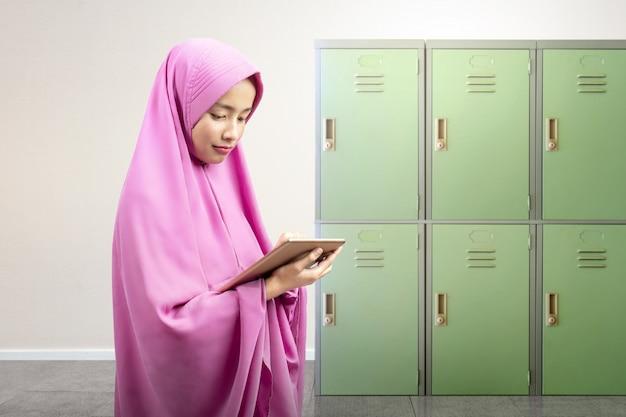 Mulher muçulmana asiática no véu usando um tablet