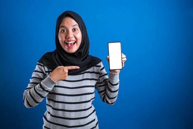 Mulher muçulmana asiática olhando para a câmera sorrindo, mostrando e apontando seu telefone inteligente