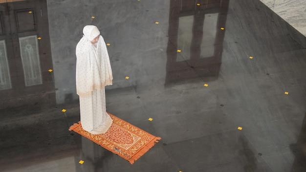 Mulher muçulmana asiática orando sozinha sem imã na mesquita