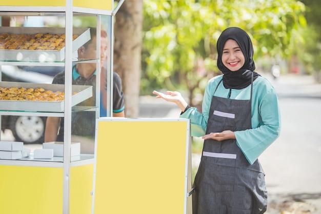 Mulher muçulmana asiática pequeno empresário e sua barraca de comida
