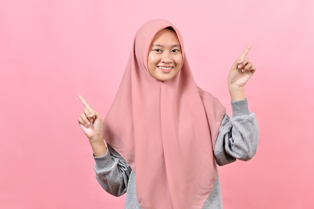 Mulher muçulmana asiática positiva aponta acima mostra lugar para seus sorrisos de texto de publicidade agradavelmente usa hijab isolado sobre fundo rosa. ótima ideia, oferta legal