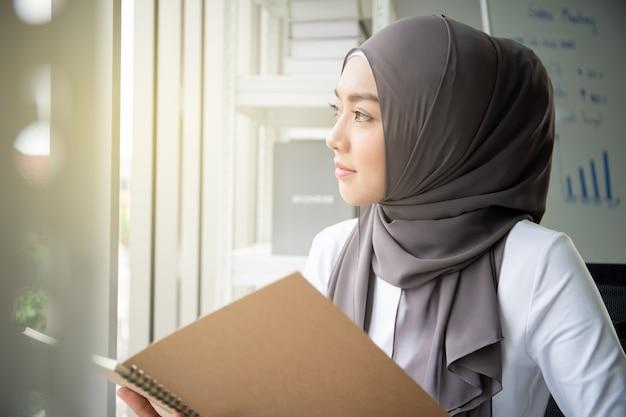Mulher muçulmana asiática que lê um livro no escritório. conceito de estilo de vida moderno povo muçulmano, retrato do muçulmano.
