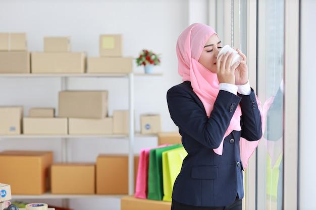 Mulher muçulmana asiática religiosa em terno azul, bebendo café, sorrindo e lenço rosa na cabeça