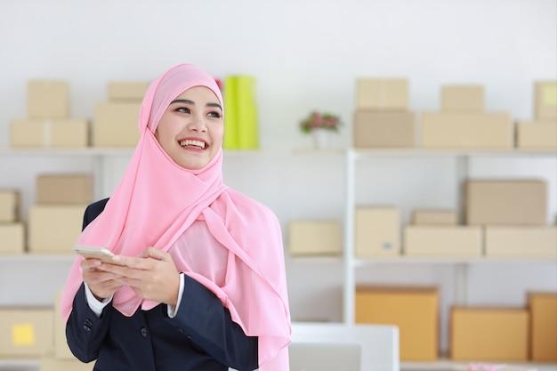 Mulher muçulmana asiática religiosa em terno azul e haste rosa na cabeça em pé, usando telefone celular e olhando para longe com uma cara feliz e confiança em fundo de entrega de caixa de pacote de negócios pme.