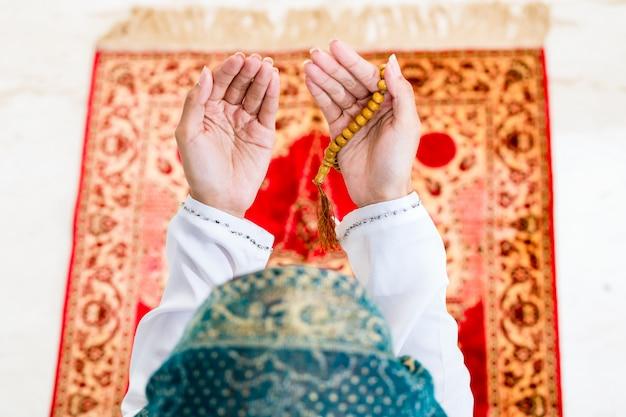 Mulher muçulmana asiática rezando com corrente de grânulos