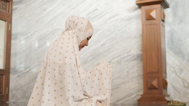 Mulher muçulmana asiática rezando esperançosamente na mesquita