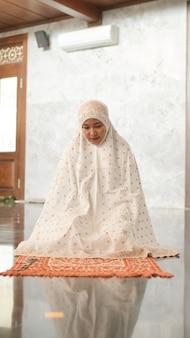 Mulher muçulmana asiática rezando na mesquita
