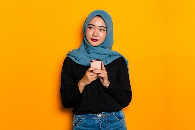 Mulher muçulmana asiática, segurando smartphone