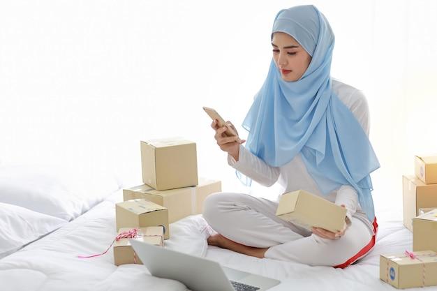 Mulher muçulmana asiática sorridente ativa em pijamas, sentado na cama, usando o telefone celular e o computador. garota freelance de pme de inicialização pequena empresa trabalhando com entrega de caixa de pacote on-line, conceito de e-commerce.