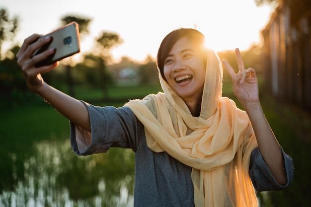 Mulher muçulmana asiática tirar selfie com telefone móvel