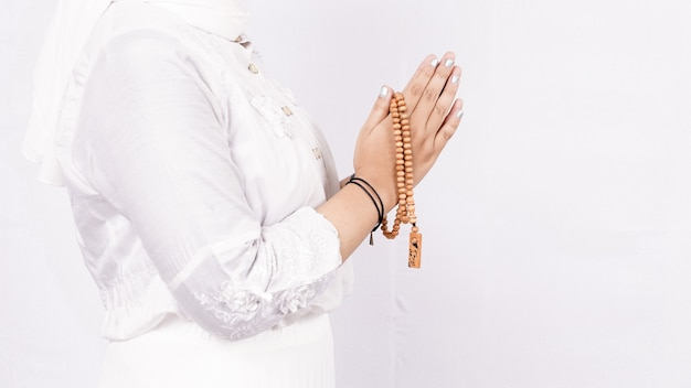 Mulher muçulmana asiática usando contas de oração dando as boas-vindas aos convidados ou saudação ied fitr no espaço em branco