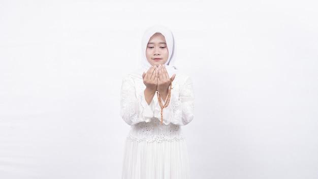 Mulher muçulmana asiática usando contas de oração orando em branco