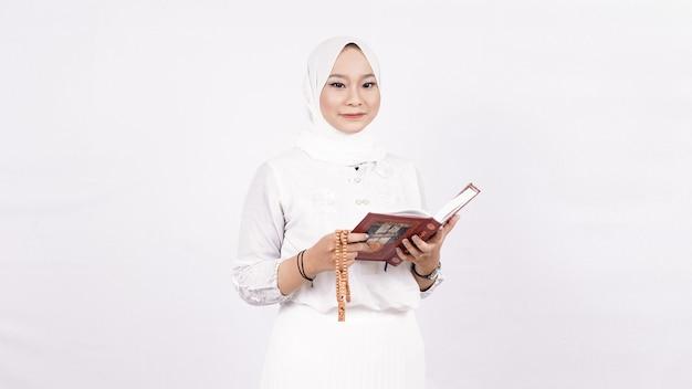 Mulher muçulmana asiática usando contas de oração rezando no espaço em branco