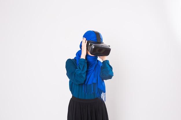 Mulher muçulmana asiática usando hijab usando óculos de fone de ouvido vr de realidade virtual em fundo branco.
