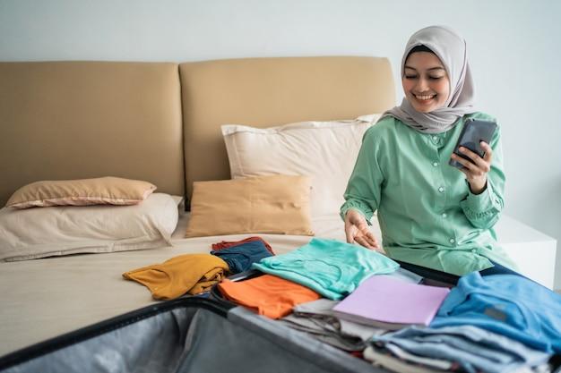Mulher muçulmana asiática usando seu telefone celular com mala cheia