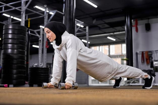 Mulher muçulmana ativa em hijab tendo treinamento intenso fazendo prancha de flexões com halteres. exercícios de crossfit na academia, conceito de esporte