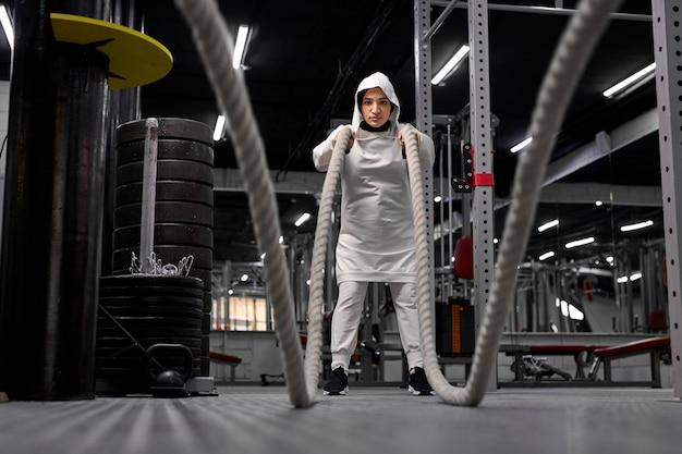 Mulher muçulmana atlética malhando com cordas na cruz fit ginásio copyspace confiança motivação esportes estilo de vida atividade passatempo saudável poderoso conceito de treinamento de feminilidade
