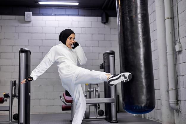Mulher muçulmana batendo no saco de pancadas com as pernas, forte mulher árabe exercitando-se sozinha no centro de fitness, usando hijab. esporte, fitness, conceito de boxe