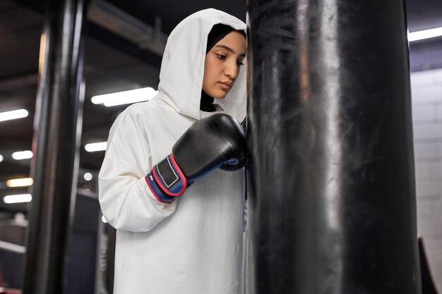 Mulher muçulmana batendo no saco de pancadas, forte mulher árabe exercitando-se sozinha no centro de fitness, usando hijab. esporte, fitness, conceito de boxe