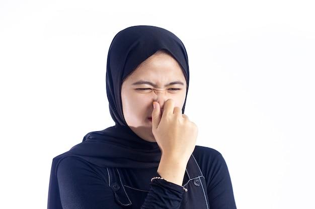 Mulher muçulmana beliscando o nariz com nojo no rosto devido ao mau cheiro isolado sobre fundo branco