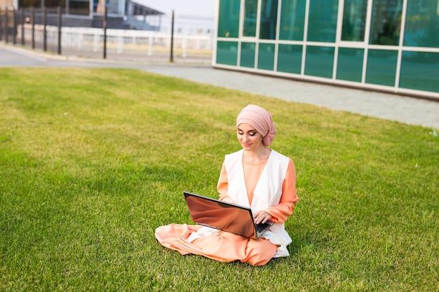 Mulher muçulmana bem-sucedida e empresária árabe com laptop usando hijab e trabalhando em um laptop no parque