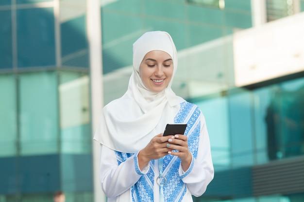 Mulher muçulmana bonita que texting em um telefone móvel ao ar livre.