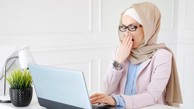Mulher muçulmana cansada de óculos e hijab no final do dia de trabalho está digitando no laptop e bocejando no local de trabalho.